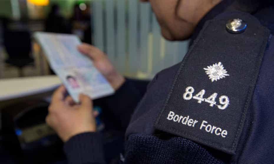 Border Force official inspects a passport