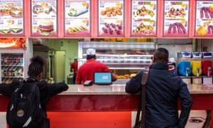 Customers wait at the counter of a chicken shop in London