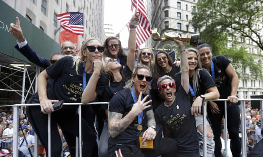 Megan Rapinoe holds the Women's World Cup trophy on the parade float.
