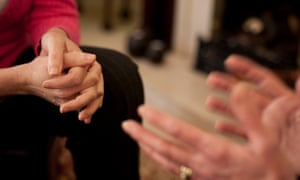 Close up of a counsellor's clasped hands as she listens to a client.