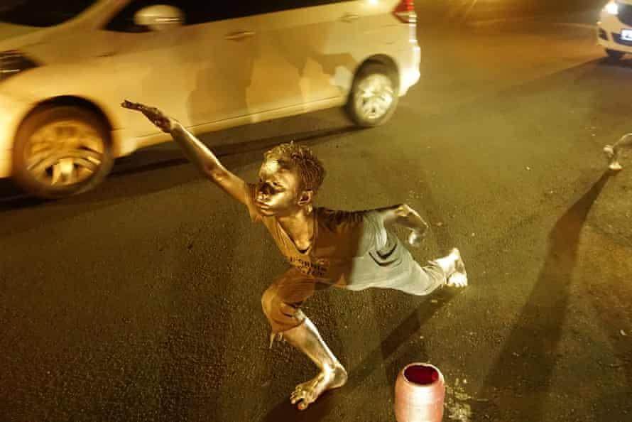 A 'silverman' begs for money in Jakarta.