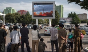 People watch footage of a rocket launch in Pyongyang