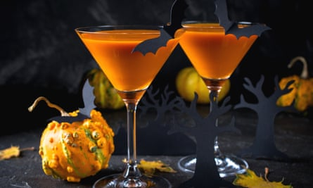 Orange martini cocktails with bats and decor for Halloween party