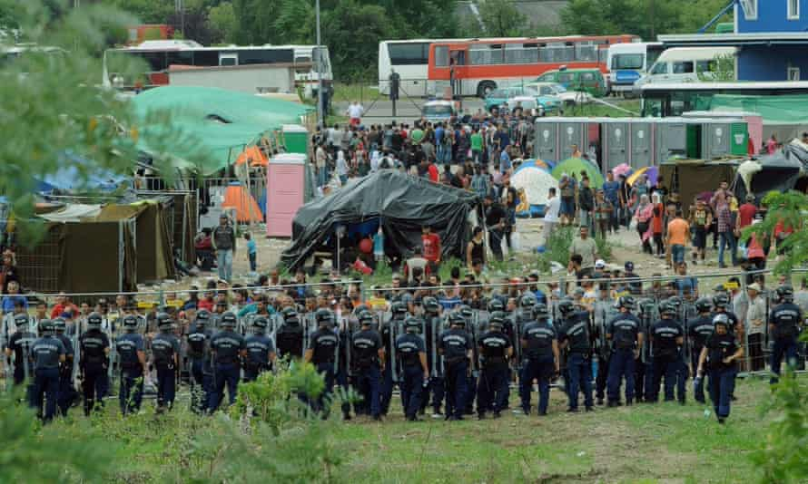 Police officers guard a refugee camp in the village of Röszke at the Serbian-Hungarian border.
