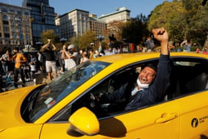 A cab driver in New York, New York, raises his fist as people celebrate Joe Biden winning the US presidential election on 7 November