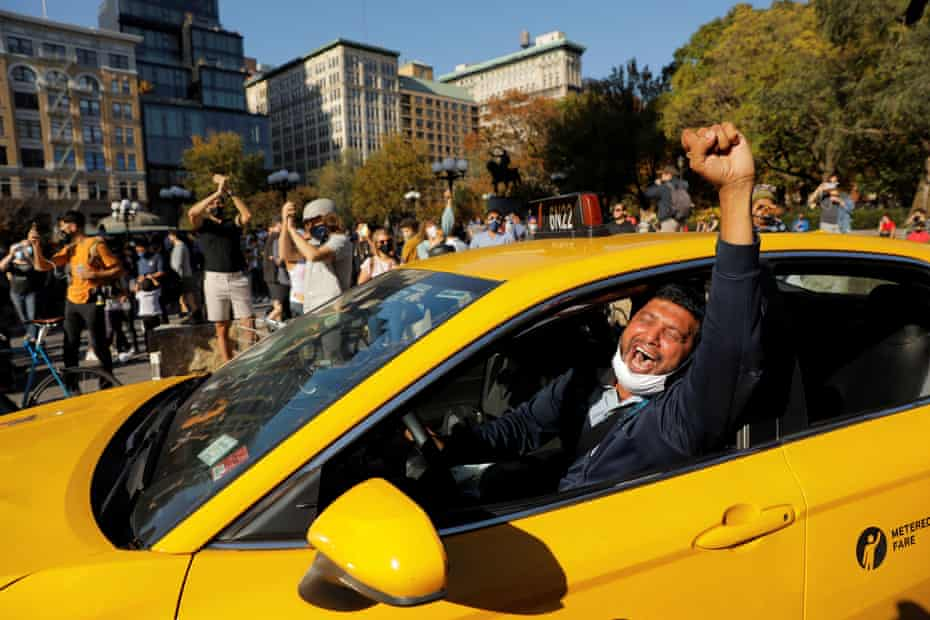 A New York yellow taxi driver raises his arm in celebration after hearing of Donald Trump's election defeat.
