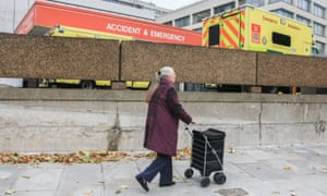 Woman pushing shopping trolley past an A&E department