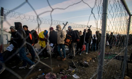 People wait in line to cross the border between Greece and Macedonia