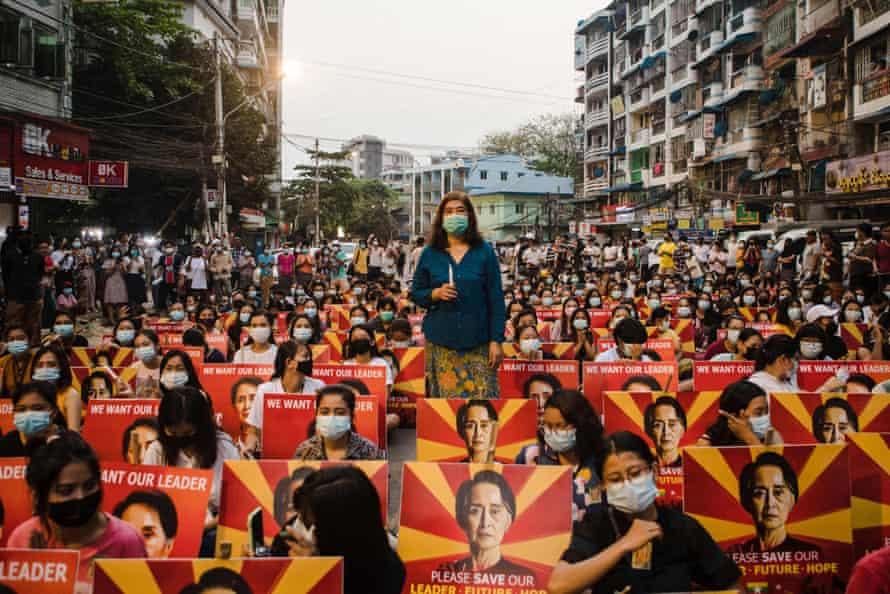 معترضین با پلاکاردهایی که تصویر رهبر غیرنظامی بازداشت شده میانمار ، آنگ سان سوچی را نشان می دهد ، قبل از برپایی مراسم شمع در هنگام تظاهرات علیه کودتای نظامی در یانگون ، در کنار خیابان نشسته اند.