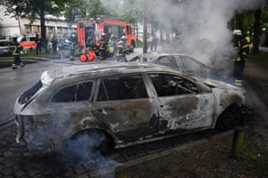 Firefighters extinguish cars set alight by protesters