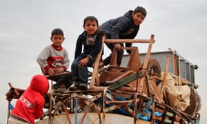Children ride on a water truck that is also loaded with furniture, near the village of Saharah, as people flee from advancing Syrian government forces in Idlib and Aleppo  provinces