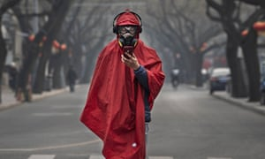 A Chinese man wears a protective mask, goggles and coat as he stands in a nearly empty street during the Chinese New Year holiday in Beijing