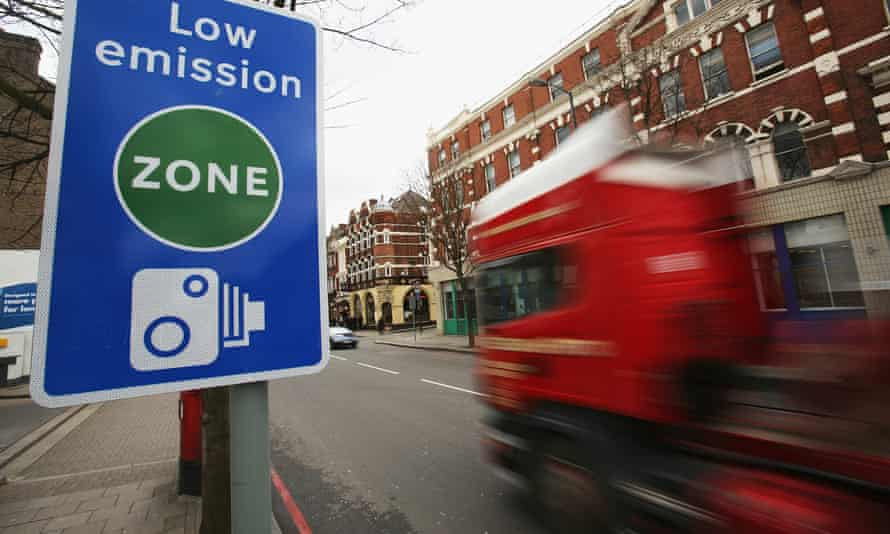 A sign saying 'low emission zone' and a red lorry driving past.