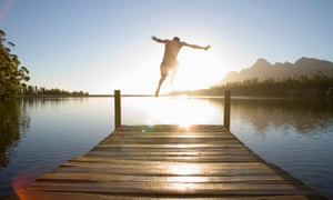 Man jumping from jetty into lake at sunset