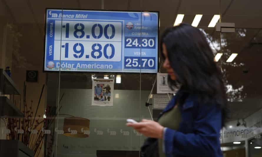 A sign displays exchange rates on a storefront window in Mexico City.