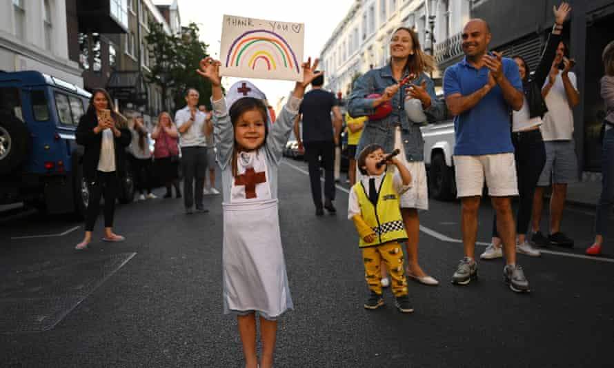 A girl wearing a nurse's uniform joins local residents in a Clap for our Carers event outside Chelsea and Westminster hospital last May.