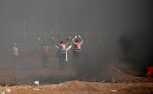 Palestinian paramedics raise their arms at Israeli snipers as they attempt to recover injured demonstrators during the clashes