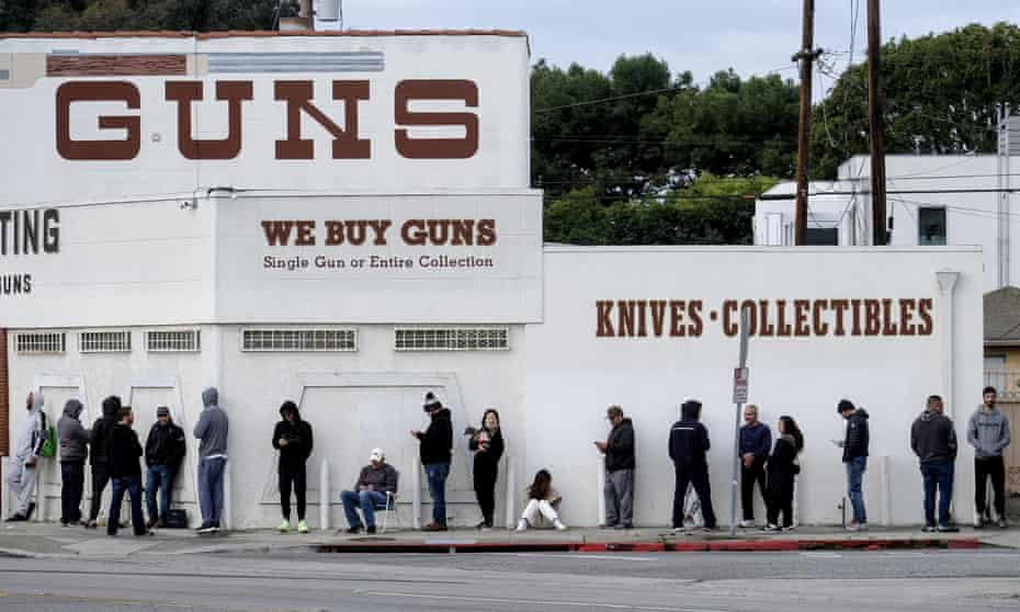 People wait in line to enter a gun store in Culver City, California, 15 March 2020.