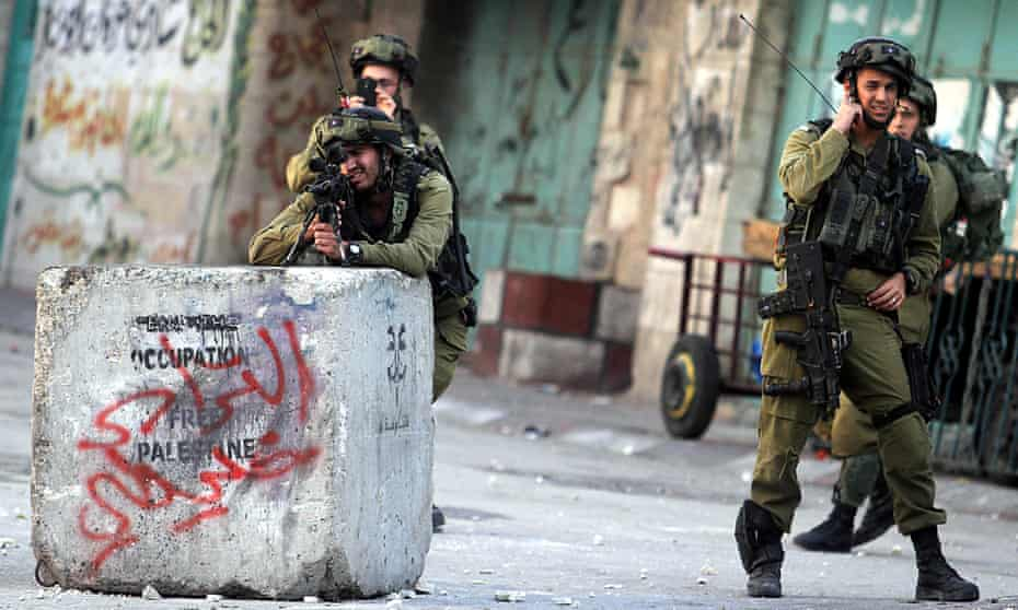 Israeli soldiers fire plastic bullets and teargas at Palestinians after the funeral of Anas al-Atrash, November 2013.