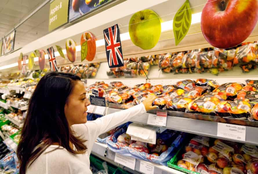 A young woman shopping buying fruit that's promoted for being local in a Waitrose supermarket, Newmarket, Suffolk, UK.