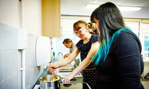 woman with learning disabilities cooking with female teacher at adult learning center kitchen