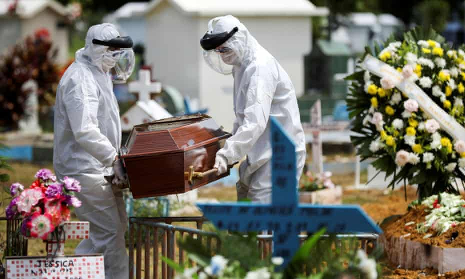 Gravediggers wearing protective suits carry the coffin of 68-year-old Natalina Cardoso Bandeira, who passed away due to coronavirus disease