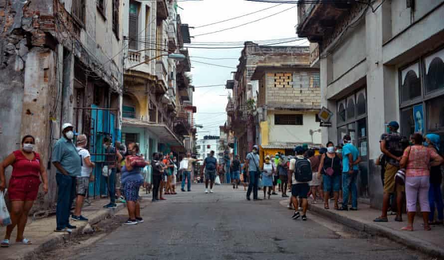 People queue to buy food in Havana.