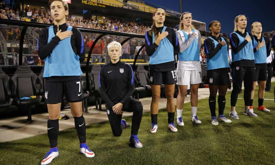 United States' Megan Rapinoe, second from left, kneels before the Thailand game.