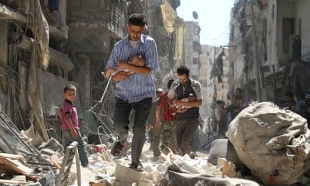 Syrian men carry babies through the rebel-held Salihin neighbourhood of Aleppo