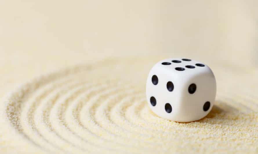 A dice landing on sand.