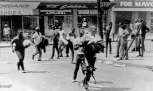 Young men carrying armloads of clothes running from looted stores, Los Angeles, California, August 1965.