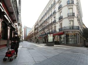 A woman walks down an empty street in Madrid