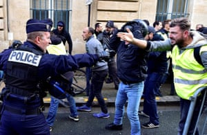 A policeman and protestor gesticulate angrily at each other.