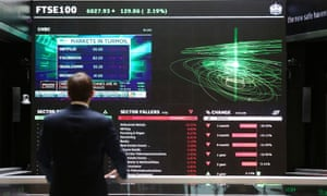 A City worker looks at a stock ticker screen at the London Stock Exchange.