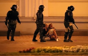 Riot police walk past two crying women during the protest