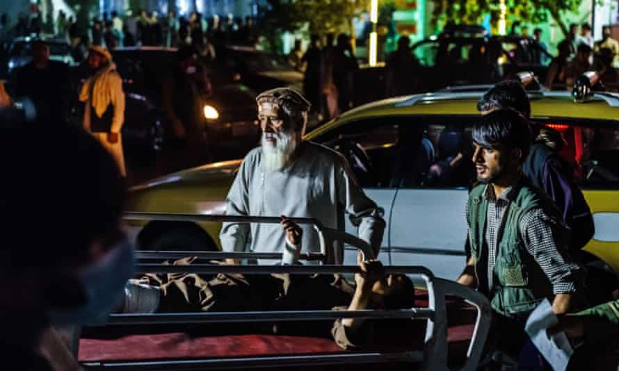 Two people push a stretcher with a wounded man through a crowded street scene at night
