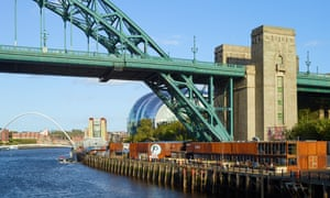 A row of red-brown shipping containers at the foot of a blue iron bridge on the banks of the river Tyne