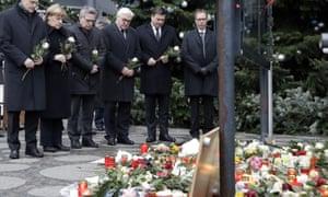 From left, the Mayor of Berlin Michael Mueller, German Chancellor Angela Merkel, German Interior Minister Thomas de Maiziere and German Foreign Minister Frank-Walter Steinmeier attend a flower ceremony at the Kaiser-Wilhelm Memorial Church in Berlin.