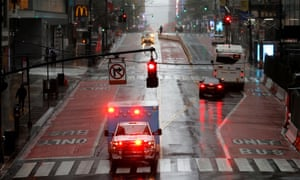 An ambulance drives across a nearly empty East 42nd Street in Manhattan during the outbreak of the coronavirus disease.