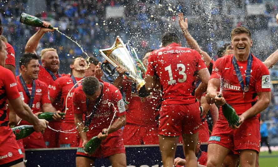 Saracens players celebrate with champagne and the Champions Cup trophy.