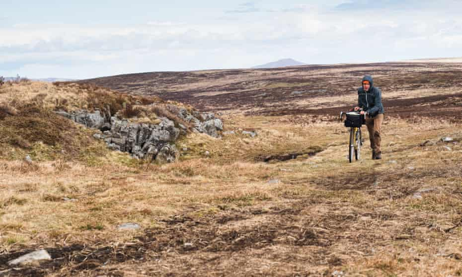 The author pushing his bike over rough ground to the Chartist Cave