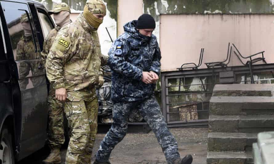 A Ukrainian sailor is escorted by a Russian FSB officer to a courtroom in Simferopol, Crimea.