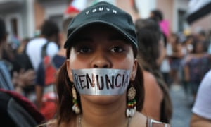 A woman wears tape over her mouth reading 'resignation' in Spanish in Puerto Rico, on 16 July.