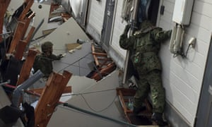 Japanese soldiers conduct search and rescue operations on Sunday after an apartment collapsed following an earthquake in Kumamoto prefecture.