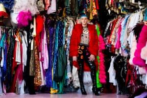 Brendan de la Hay in coloured clothes surrounded by a huge wardrobe
