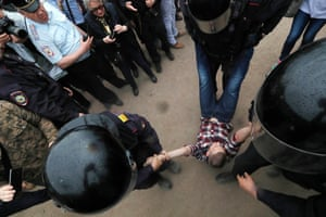 A participant in an anti-corruption rally is detained in central St Petersburg