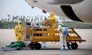 In this photo taken on 16 September 2020, ground crew spray disinfectant on luggage being unloaded from a Boeing 737-800 operated by South Korean carrier T'way after landing at Wuhan's Tianhe International Airport, in China's central Hubei province.