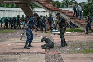 A supporter of Congolese presidential candidate Martin Fayulu protects himself as policemen close in on him outside the constitutional court in Kinshasa.