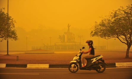 An Indonesian woman rides a motorbike amid thick haze in Palangkaraya, Central Kalimantan province, Indonesia.