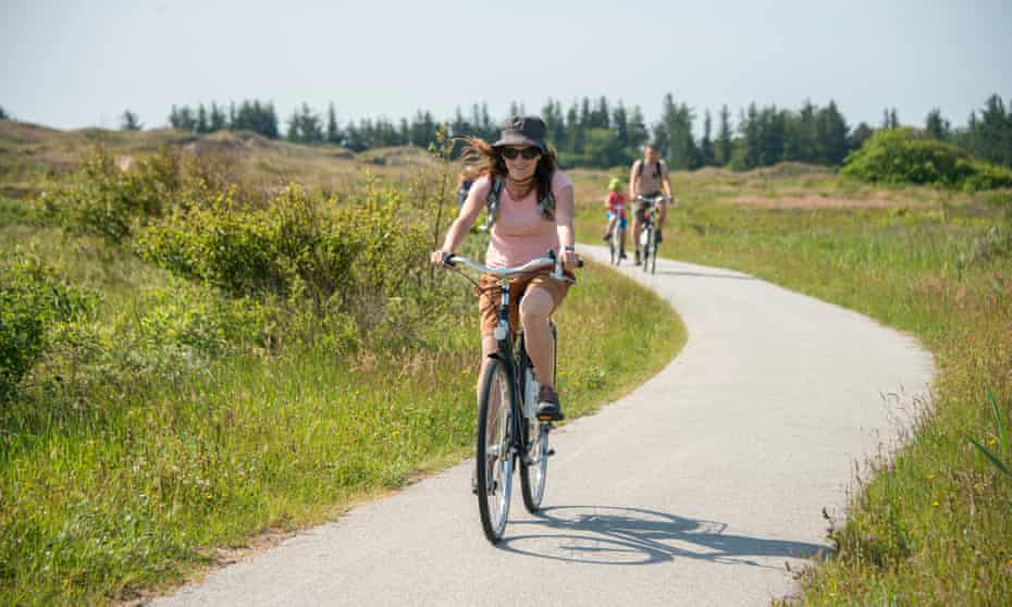 woman ride bicycle on a country road near Skagen, Denmark